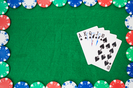 Hand of Poker, straight flush and chips frame on a felt green background. Top view and copy space.