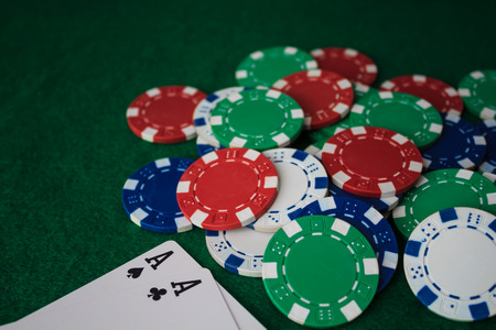 Stack of chips poker and two aces on the table on the green baize. Perspective view. Reklamní fotografie
