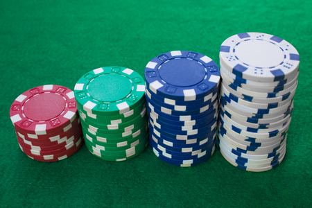 Stacks of poker chips including red, white, green and blue on a green background. Perspective view.