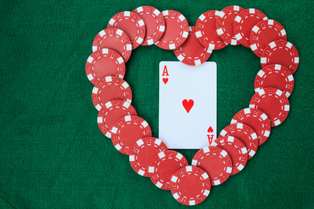 Heart made with poker chips, with an ace of hearts, on a green background table. Top view with copy space.