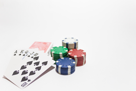 Hand of poker, Royal flush of spades, chips on white background. Stock Photo
