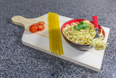 Noodles in garlic and oil, served in a bowl with bacon and tomatoe
