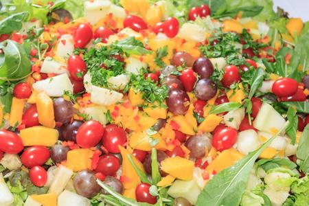 Delicious salad of vegetables and fruits. Lettuce, tomato, parsley, arugula, grape, mango, melon.