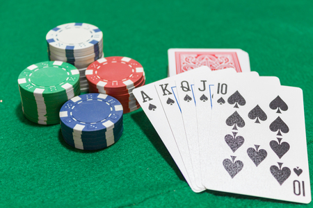 Hand of poker, Royal flush of spades, chips on green background.