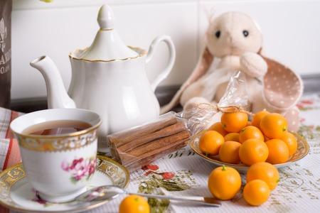 Decorative orange mandarins, tangerines, cup of tea, home mandarins, small mandarines, front view