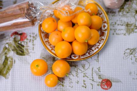 Decorative orange mandarins, tangerines, cup of tea, home mandarins, small mandarines