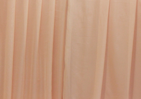 Silk in the folds of peach color, background. 免版税图像