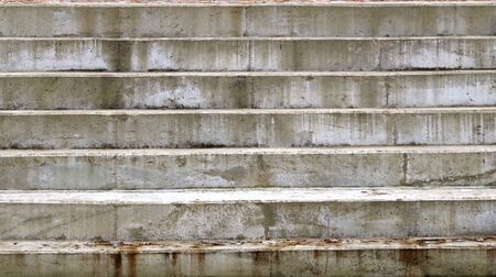 Old, stained concrete steps on the street. Imagens
