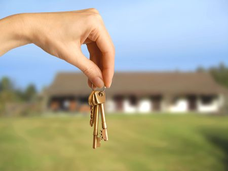 lease: female hand holding house keys in front of building