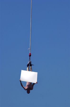man bungee jumping with a message board