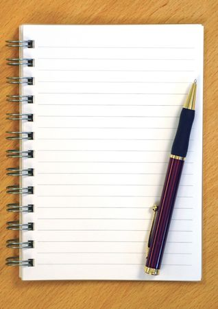 Blank notepad with pen on a wooden table