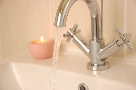 en suite: tap running into washbasin with candle in background
