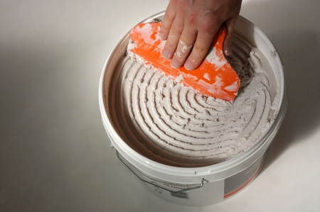 male hand scraping adhesive out of bucket with spreader