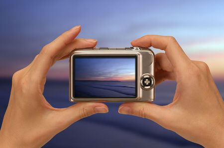 taking photo: female hands taking picture with a compact digital camera Stock Photo