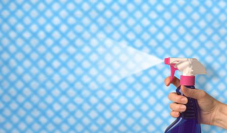 female hand spraying cleaning polish over a cloth background Stockfoto
