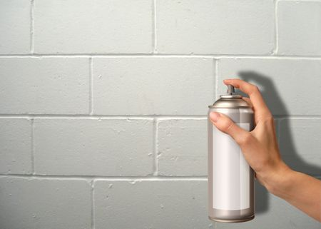 female hand using a spray cannister on a wall