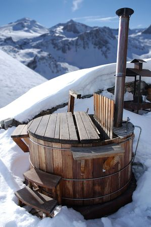 wooden hot tub in the alps with mountains behind