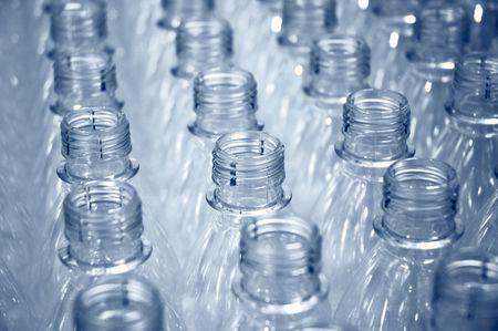 plastico pet: hileras de botellas de plástico sobre una línea de producción de la fábrica Foto de archivo