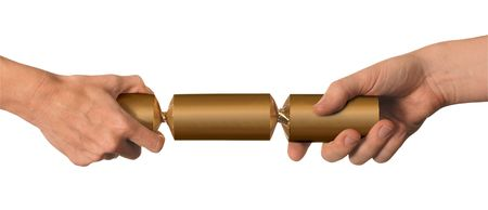 christmas cracker: male and female hands pulling a gold christmas cracker