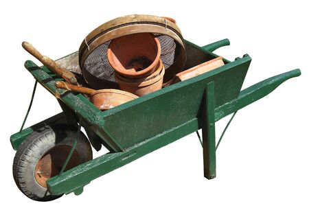 old wooden wheelbarrow full of gardening tools and equipment Stock Photo