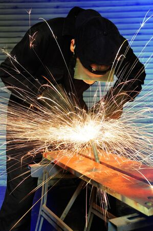 factory worker creating sparks whilst grinding metal photo