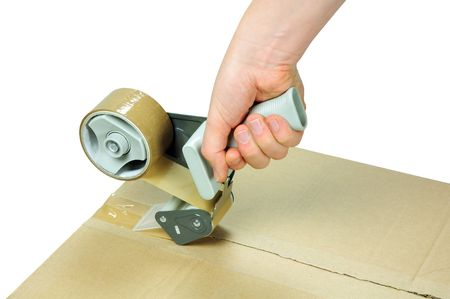 packaging move: sealing cardboard box with adhesive packing tape