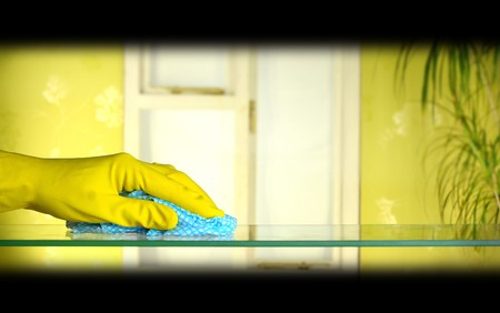 dusting: cleaning glass using cloth and yellow rubber gloves