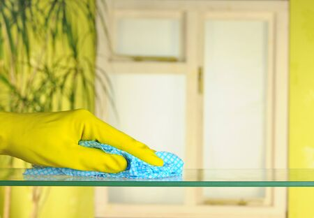 person in rubber gloves using a blue duster
