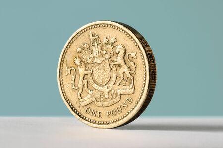 pound sterling: Una moneda de libra se puso de pie sobre un fondo azul con copia espacio