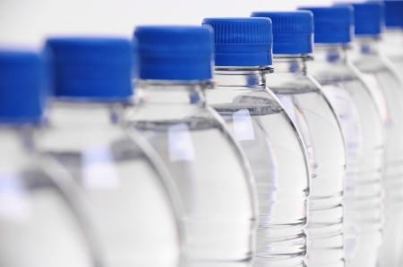 select focus on middle bottle in a row of water bottles photo