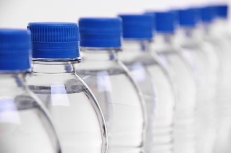 botellas pet: fila de tapas de botellas de agua con un enfoque de selección en la segunda botella Foto de archivo