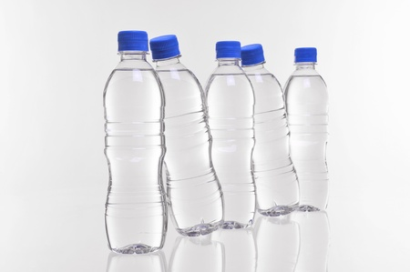 plastico pet: cinco botellas de agua con dos en un ángulo Foto de archivo