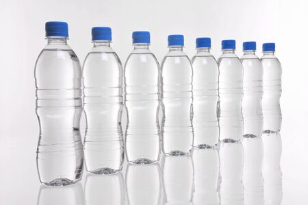 Eight water bottles with blue lids in a row Stockfoto