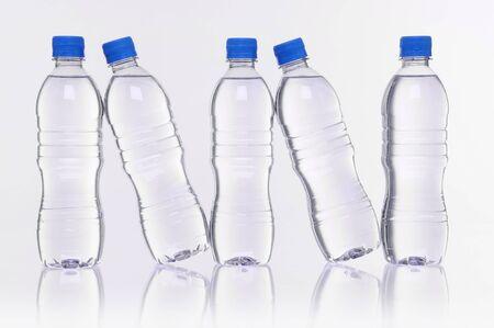 plastico pet: fila de cinco botellas de agua con la reflexión Foto de archivo