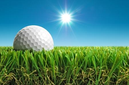 近距离的高尔夫球在草地与太阳的背景