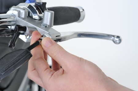 hand brake: mechanic adjusting the front brake on a motorcycle