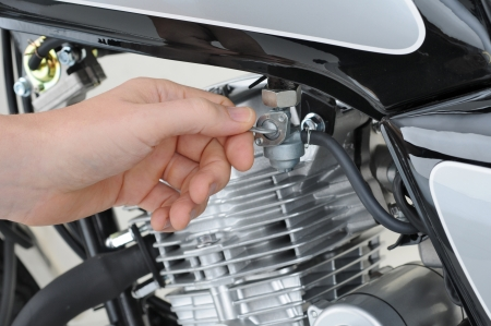 mechanic checking the petrol tap on a motorcycle