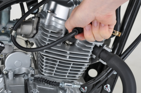 mechanic checking the spark plug lead on a motorcycle Stock fotó - 15305315
