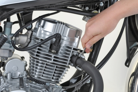mechanic tightening the exhaust on a motorcycle engine Stock Photo