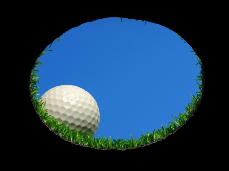 Golf ball: pelota de golf en el borde de un hoyo de golf, visto desde abajo