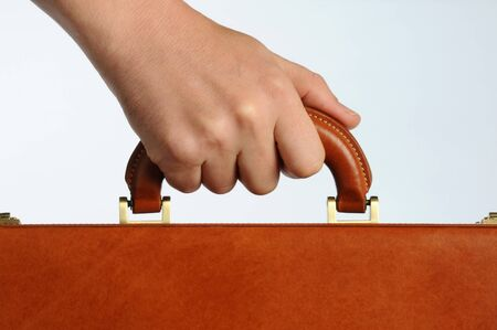 businessman holding the handle of a brown leather briefcase