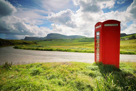 Phone booth in the middle of a green field photo