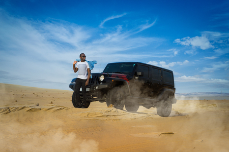 Young guy Posing on desert during offload race