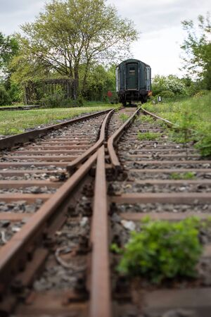turnout: An old railway switch out of focus and in the background an old wagon. Stock Photo