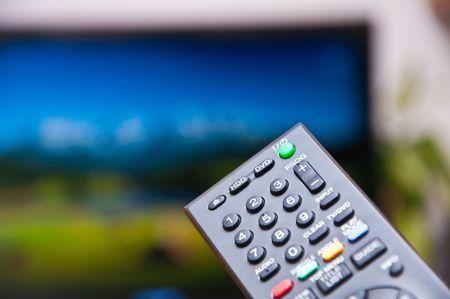 davenport: Black remote control changing channel on TV