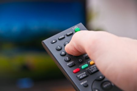 changing channel: Black remote control changing channel on TV