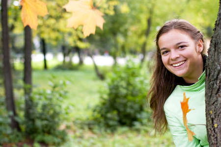 smiling girl and falling maple leaves in autumn photo