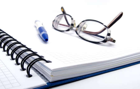 blank notebook with pen and glasses on white background photo