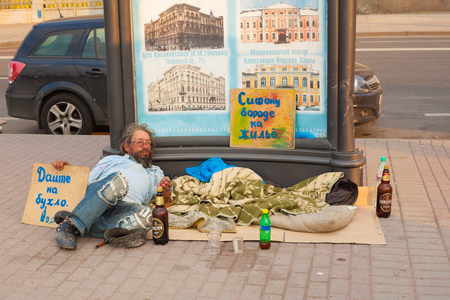 alms: homeless man lying in the street alms in Russia. Saint-Petersburg