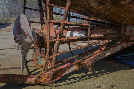 Detail of a rusty ship on the shore: the propeller in it39s cage. Some orange rope wrapped around it. photo